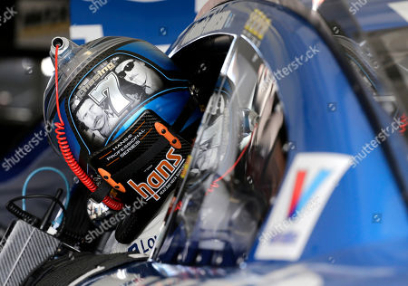 Jimmie Johnson gets in his car as he prepares for the NASCAR Sprint Cup Series auto practice, in Homestead, Fla. On the back of Johnson's helmet, Dale Earnhardt, left, and Richard Petty, right are pictured, both have seven series championships, as Johnson with six championships is chasing his seventh