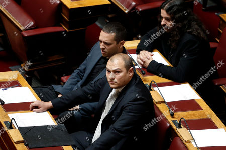 May 7, 2014, the extreme right Golden Dawn party lawmaker Georgios Germenis, front, sits with Costas Barbarousis, top right, and Ilias Kasidiaris, both Golden Dawn members of the parliament, during a parliament session in Athens. Greek police say Germenis has been briefly hospitalized after being set upon by a group of people, possibly anarchists, who hit him with an iron bar and sprayed him with pepper spray on