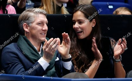 German footballer Bastian Schweinsteiger and wife Ana Ivanovic applaud during the ATP World Tour Finals singles final tennis match between Andy Murray of Britain and Novak Djokovic of Serbia at the O2 Arena in London