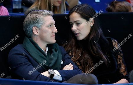 German footballer Bastian Schweinsteiger and wife Ana Ivanovic chat during the ATP World Tour Finals singles final tennis match between Andy Murray of Britain and Novak Djokovic of Serbia at the O2 Arena in London