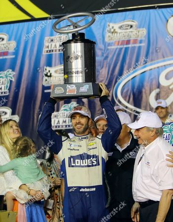 Jimmie Johnson, Chandra Johnson, Edsel Ford Jimmie Johnson holds up the race winners trophy as his wife Chandra and Edsel Ford, right, looks on after NASCAR Sprint Cup auto race, in Homestead, Fla