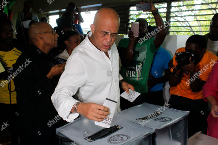 Haiti's former President Michel Martelly casts his ballot during elections in the Petion-Ville suburb of Port-au-Prince, Haiti, . Haiti's repeatedly derailed presidential election got underway more than a year after an initial vote was annulled