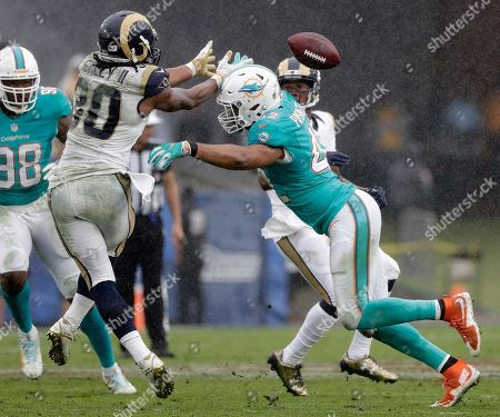 Miami Dolphins linebacker Spencer Paysinger breaks up a pass intended for Los Angeles Rams running back Todd Gurley, left, during the second half of an NFL football game, in Los Angeles