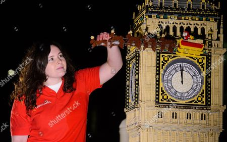 Stock Picture of LEGOLAND® model maker Amanda Green puts the finishing touches to LEGO Rudolph flying across Big Ben.
