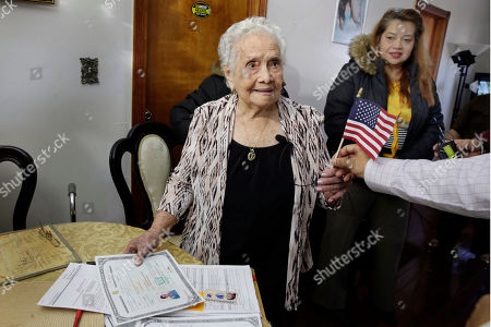 Maria Martinez, Monica Martinez America Maria Hernandez, 99, receives an American flag after being administered the Naturalization Oath of Allegiance, in the Queens borough of New York. The Colombian immigrant, who was brought to the U.S. by one of her daughters in 1988, signed her naturalization certificate and took the oath of allegiance in her living room, surrounded by family members and TV cameras. Looking on at right is her granddaughter Monica Martinez