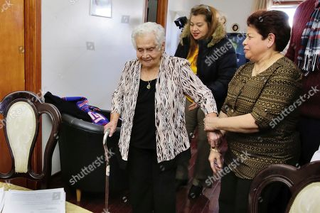 Maria Martinez, Monica Martinez, Ana Martinez America Maria Hernandez, 99, left, is aided by her granddaughter Monica Martinez, center, and daughter Ana Martinez as she prepares to take the Naturalization Oath of Allegiance, in the Queens borough of New York. The Colombian immigrant, who was brought to the U.S. by one of her daughters in 1988, signed her naturalization certificate and took the oath of allegiance in her living room, surrounded by family members and TV cameras