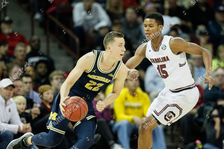 Stock Picture of Duncan Robinson (22) of the Michigan Wolverines drives by PJ Dozier (15) of the South Carolina Gamecocks in the NCAA Basketball matchup between the Michigan Wolverines and the South Carolina Gamecocks at Colonial Life Arena in Columbia, SC