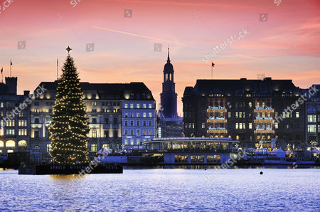 Binnenalster or Inner Alster Lake at Christmas time with Alster fir tree and Church of St. Michael, Michaeliskirche, Michel, Hamburg, Germany