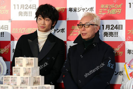 """Japanese actors Go Ayano (L) and Geoge Tokoro (R) display one billion yen (9 million US dollars) in cash for the """"Year-end Jumbo Lottery"""" as the first tickets go on sale in Tokyo on Thursday, November 24, 2016. Thousands of punters queued up for tickets in the hope of becoming a billionaire in the annual lottery."""