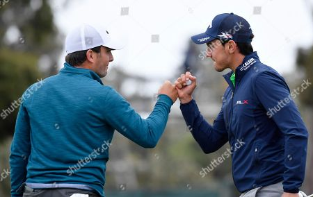 Italy's Francesco Molinari, left, and Italy's Matteo Manassero celebrate on the 18th green at the completion of their match at the World Cup of Golf at Kingston Heath in Melbourne, Australia