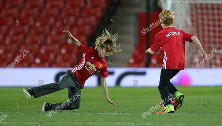 Stock Picture of HENRY MODER FALLS OVER AND  PHINNAEUS MODER  [JULIA ROBERTS CHILDREN] ON MANCHESTER UNITED PITCH AFTER THE MATCH PLAYS FOOTY
