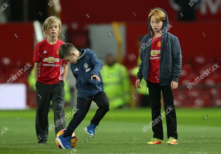 Stock Picture of PHINNAEUS AND HENRY MODER WATCH KLAY ROONEY JUGGLE WITH FOOTBALL ON MANCHESTER UNITEDS PITCH AFTER MATCH