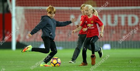 Stock Photo of PHINNAEUS MODER [JULIA ROBERTS CHILD] ON MANCHESTER UNITED PITCH AFTER THE MATCH PLAYS FOOTY WITH BROTHER HENRY AND FRIEND GEORGIA