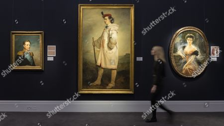 """A staff member walks in front of three royal portraits (L to R) """"Nicholas I"""" (est GBP 40-60k), """"Prince Paul Demidoff"""" (est GBP 40-60k) and """"Grand Duchess Elena Vladimirova"""" (est GBP 18-25k), at the preview of artworks from Sotheby's upcoming Russian sales"""
