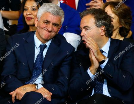French politicians Herve Morin, left, and Luc chatel chat as they support Francois Fillon, a candidate in Sunday's primary runoff to select a conservative candidate for the French presidential election, during a rally in Paris, . Fillon, a champion of free-market economics and traditional family values must defeat Alain Juppe a moderate who accuses his rival of pandering to the far right. Woman at right is unidentified