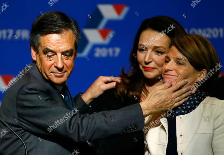 Francois Fillon, a candidate in Sunday's primary runoff to select a conservative candidate for the French presidential election, has a gesture for close aide Valerie Boyer, center behind, and Chantal Jouanno during a rally in Paris, . Fillon, a champion of free-market economics and traditional family values must defeat Alain Juppe a moderate who accuses his rival of pandering to the far right