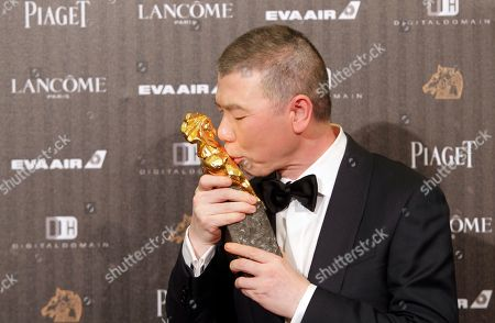 """Feng Xiaogang Chinese director Feng Xiaogang kisses his award for Best Director at the 53rd Golden Horse Awards in Taipei, Taiwan, . Feng won for the film """"I Am Not Madame Bovary"""" at this year's Golden Horse Awards -the Chinese-language film industry's biggest annual events"""