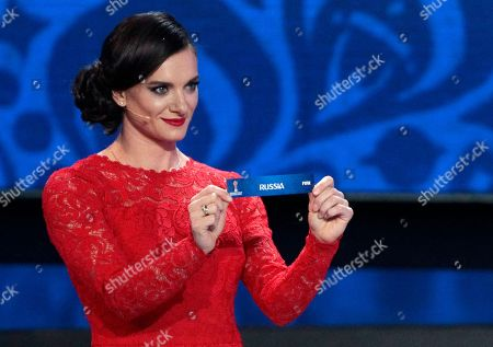 Former Russian pole vaulter Yelena Isinbayeva holds the lot of Russia during the draw for the soccer Confederations Cup 2017, in Kazan, Russia, . The tournament will be played June 17 trough July 2, 2017 in four Russian cities