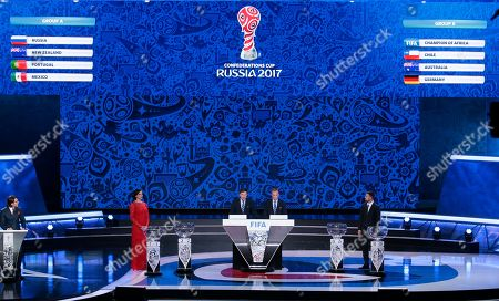 Former Russian pole vaulter Yelena Isinbayeva, Zvonimir Boban, FIFA's Deputy Secretary General for Football, Colin Smith, FIFA's director of competition, and former Russian soccer player Sergei Semak, from left, stand on the stage in front of the drawing results during the draw for the soccer Confederations Cup 2017, in Kazan, Russia, . Russia, New Zealand, Portugal and Mexico play in group A, The African Champion, Chile, Australia and Germany in group B