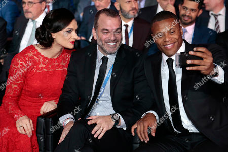Brazilian soccer player Julio Baptista, right, takes a selfie with Fabiano Prata Farah and former Russian pole vaulter Yelena Isinbayeva, left, prior to the draw for the soccer Confederations Cup 2017, in Kazan, Russia, . The tournament will be played June 17 trough July 2, 2017 in four Russian cities