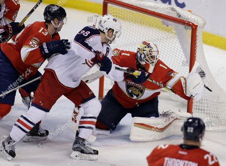 Roberto Luongo, Mark Pysyk, Boone Jenner Florida Panthers goalie Roberto Luongo (1) makes a save as defenseman Mark Pysyk (13) defends against Columbus Blue Jackets center Boone Jenner (38) during overtime of an NHL hockey game, in Sunrise, Fla