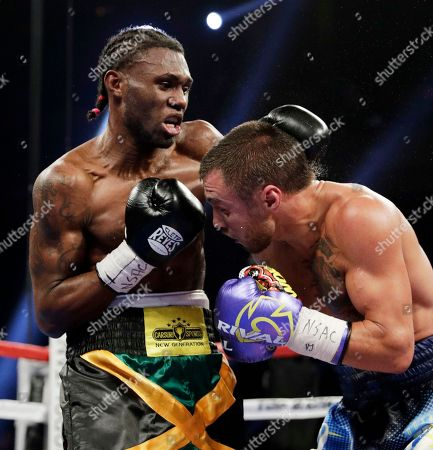 Nicholas Walters, left, of Jamaica, hits Vasyl Lomachenko, of Ukraine, in a WBO junior lightweight title boxing match, in Las Vegas