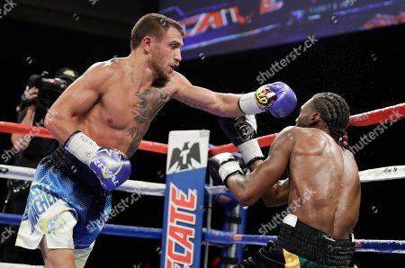 Vasyl Lomachenko, left, of Ukraine, hits Nicholas Walters, of Jamaica, during a WBO junior lightweight title boxing match, in Las Vegas
