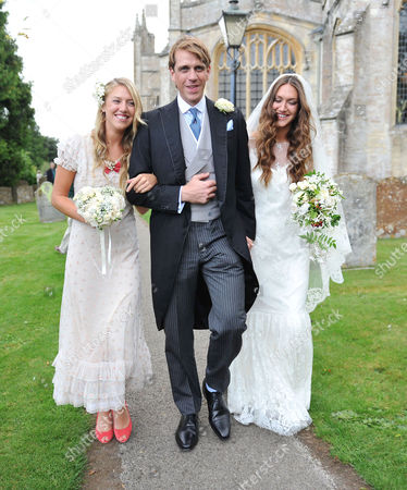 Wedding of Ben Elliot and Mary-clare Winwood at the Church of St Peter and St Paul Northleach Cheltenham the Bride and Groom After the Service with the Maid of Honour Eliza Winwood