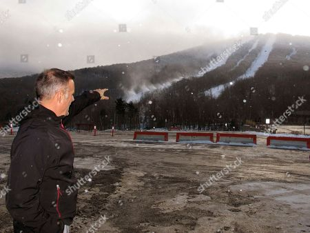 Stock Image of Steve Wright, general manager at Jay Peak Resort, points out at new snowmaking guns blowing snow onto a lower trail of the resort in Jay, Vt. Seven months after the Securities and Exchange Commission accused Jay Peak's owner of misappropriating millions of dollars in foreign investors' money, the resort is expected to officially open for the ski season on Saturday