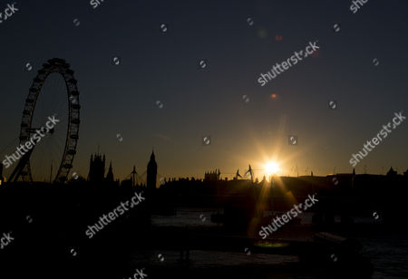 The view West toward the cityscape of Millennium Wheel London Eye, Big Ben Elizabeth Tower, Victoria Tower and Westminster Abbey at sunset.