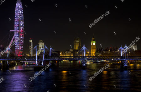 Stock Image of The night view West towards Millennium Wheel/London Eye, Big Ben/Elizabeth Tower, Victoria Tower, Millbank and Westminster Abbey (right). Central London landmarks