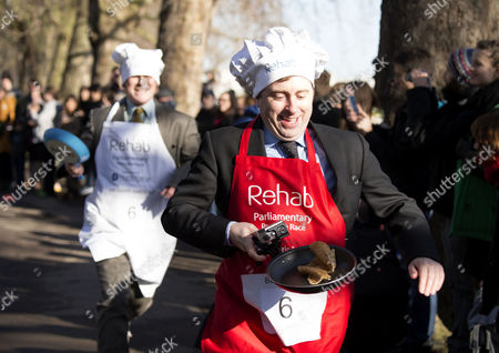 the Rehab Parliamentary Pancake Race Mps Lords Political Correspondents and Members of the Media Compete in the Fundraiser Organised by the Rehab Disability Charity to Support the Its Work with Disabled People at Victoria Tower Gardens Westminster Ben Wright of the Bbc & Sir David Amess Mp ( Southend West)