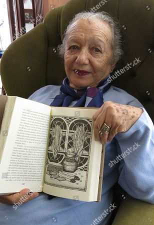 """Socorro Gordillo, wife of Mexican writer Fernando del Paso, poses with their book """"La cocina Mexicana,"""" in Guadalajara Mexico. The couple presented the new edition of the book about Mexican ingredients and recipes at the Guadalajara International Book Fair"""