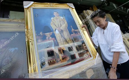 A shopkeeper places portraits of Thailand's Crown Prince Vajiralongkorn outside her shop in Bangkok, Thailand, . Thailand is preparing to welcome a new king with final arrangements scheduled to formalize the accession of Crown Prince Maha Vajiralongkorn to the throne