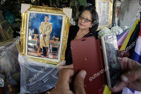 A shopkeeper show portraits of Thailand's Crown Prince Vajiralongkorn to a customer outside of her shop in Bangkok, Thailand, . Thailand is preparing to welcome a new king with final arrangements scheduled to formalize the accession of Crown Prince Maha Vajiralongkorn to the throne