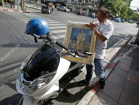 A customer purchases a portrait of Thailand's Crown Prince Vajiralongkorn in Bangkok, Thailand, . Thailand is preparing to welcome a new king with final arrangements scheduled to formalize the accession of Crown Prince Maha Vajiralongkorn to the throne