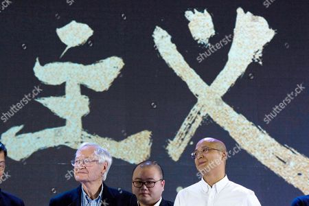"""American film producer Roger Corman, left, and Yang Xianghua, iQIYI's senior vice president, right, attend a news conference to announce co-production between Chinese online video site iQIYI and Sony Pictures in Beijing, China, . The 90-year-old American producer of films including """"The St. Valentine's Day Massacre"""" and """"Attack of the 50 Foot Cheerleader"""" will lead a team of young Chinese filmmakers and act as producer on a sci-fi film made for viewing on the internet or mobile phone called """"Invasion"""