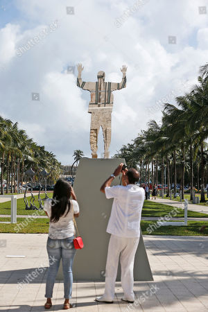 """Stock Picture of A couple photographs a sculpture titled: """"Invisible Man"""" (2016) by artist Glenn Kaino, being displayed in front of the Bass Museum of Art, in Miami Beach, Fla. Miami's art world does not stop for Zika-carrying mosquitoes. Poolside parties, outdoor red carpets and blocks upon blocks of art fairs are continuing as planned this week for Art Basel Miami Beach. Concern that the festival would be thwarted had flared in July when the first cases of Zika transmission through mosquito bites on the U.S. mainland were reported in Wynwood and later in nearby Miami Beach. While part of Miami Beach continues to be officially considered an active transmission zone, health officials have declared outbreaks both in Wynwood and other sections of Miami Beach to be over"""