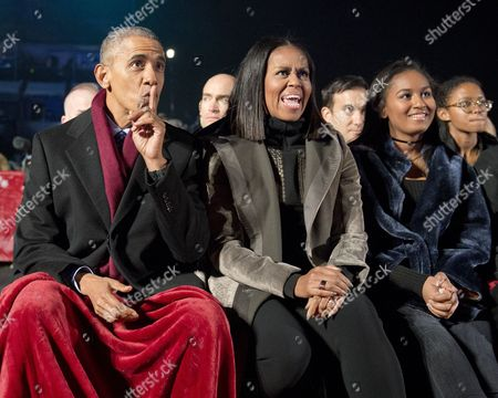United States President Barack Obama, first lady Michelle Obama and Sasha Obama watch the entertainment as they attend the National Christmas Tree Lighting on the Ellipse in Washington, DC.