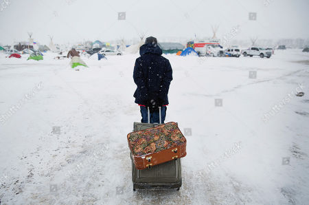 Cody Wolfchild, a Sioux Native American, pulls suitcases through the snow at Oceti Sakowin camp where people have gathered to protest the Dakota Access oil pipeline in Cannon Ball, N.D. Camp dwellers are getting ready for the hardships of a long stay. Mountains of donated food and water are being stockpiled, as is firewood, much of which has come from outside of North Dakota, the least-forested state in the nation