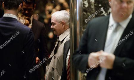 Former United States Secretary of Defense Robert Gates (C) enters an elevator