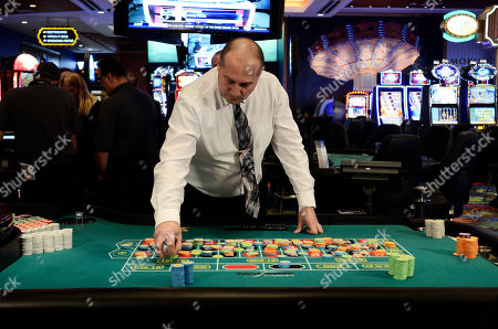 Tioga Downs Director of Casino Operations, Mike Chapman, simulates a roulette game during a media tour before the official opening of the new gaming floor, in Nichols, N.Y. The first of four planned casinos opened with a flurry of balloons, confetti and uncertain visions of economic resurgence on Friday as New York ushered in a new era of state-sanctioned gambling aimed at reversing decades of upstate decline