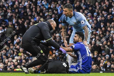 Aleksander Kolarov attempts to get Diego Costa off the pitch for treatment