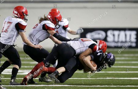 Odessa-Harrington running back Josh Clark, right, is tackled by Neah Bay linebacker Nate Tyler, second from right, in the first half of the Washington Div. 1B high school football championship, in Tacoma, Wash