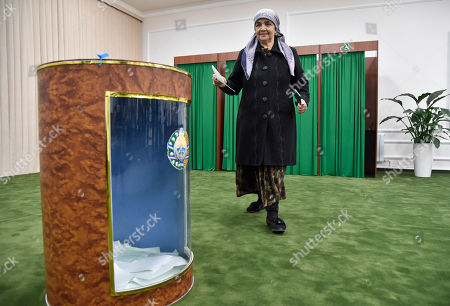 A Uzbek woman walks to cast her ballot during tightly controlled presidential election, the first vote since the death of authoritarian leader Islam Karimov who ruled the country for 27 years, in Tashkent, Uzbekistan, . The odds-on favorite is acting President Shavkat Mirziyoyev, who spent 13 years as Karimov's prime minister