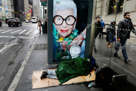Iris Apfel, Daily Life A homeless man sleeps under a blanket in a Fifth Avenue bus shelter, in New York