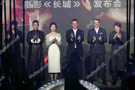 """Actors and actress from right, Willem Dafoe, Pedro Pascal, Matt Damon, Jing Tian, Andy Lau, Zhang Hanyu, applaud on stage as movie director Zhang Yimou arrives for a news conference for the movie """"The Great Wall"""" at a hotel in Beijing"""