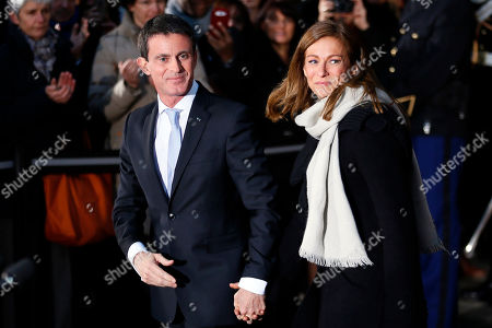 Outgoing Prime Minister Manuel Valls, left, and his wife Anne Gravoin leave after the hand over ceremony in Paris, Tuesday, Dec.6, 2016. Valls stepped down Tuesday to focus on running for president in next year's election and was replaced by Interior Minister Bernard Cazeneuve, a man who embodies the fight against Islamic extremism