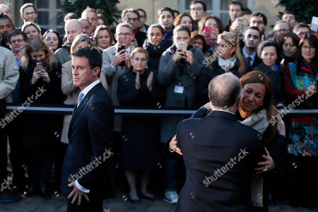 Outgoing Prime Minister Manuel Valls, left, looks on as his wife Anne Gravoin, right, kisses new Prime Minister Bernard Cazeneuve after the hand over ceremony in Paris, Tuesday, Dec.6, 2016. Valls stepped down Tuesday to focus on running for president in next year's election and was replaced by Interior Minister Bernard Cazeneuve, a man who embodies the fight against Islamic extremism