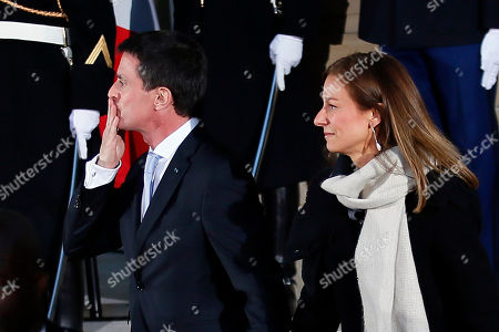 Outgoing Prime Minister Manuel Valls, blows a kiss flanked with his wife Anne Gravoin, as they leave after the hand over ceremony in Paris, Tuesday, Dec.6, 2016. Valls stepped down Tuesday to focus on running for president in next year's election and was replaced by Interior Minister Bernard Cazeneuve, a man who embodies the fight against Islamic extremism